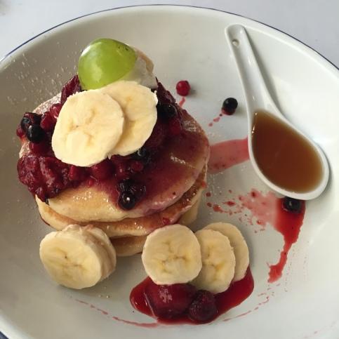 Pancakes dulces con sirope de arce y frutos rojos